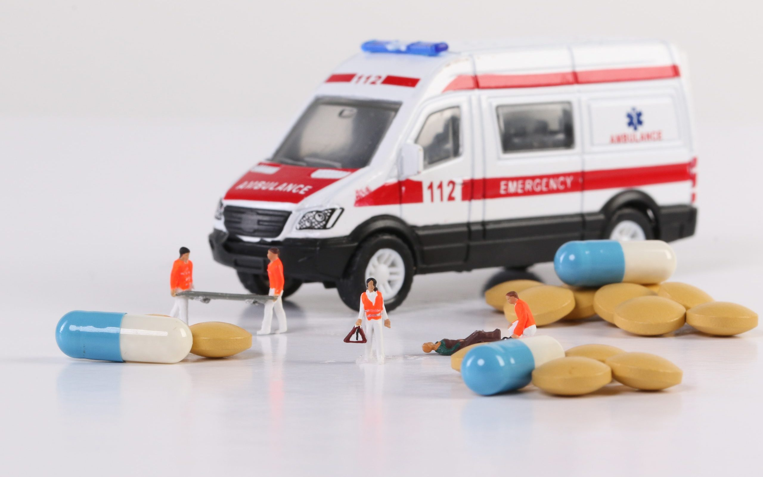 Ambulance crew helping unconscious and injured people on ground,
